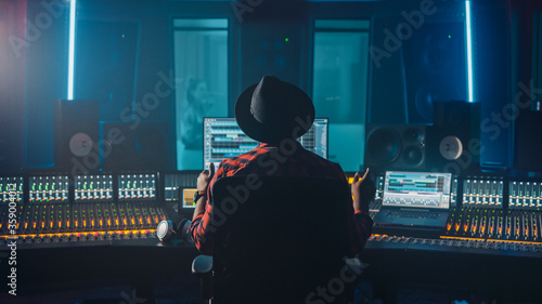 Fototapeta Producer, Audio Engineer Uses Control Desk for Recording New Album Track in Music Record Studio, in the Soundproof Room Musician, Artist, Performer Sings a Song from New Album. Back View  obraz