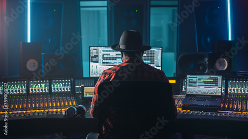 Obraz na plátně Stylish Artist, Musician, Audio Engineer, Producer Takes Place at His Control Desk in Music Record Studio, Uses Computer Screen show User Interface of DAW Software with Song Playing