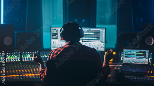 Artist, Musician, Audio Engineer, Producer in Music Record Studio, Uses Control Desk with Computer Screen showing Software UI with Song Playing Slika na platnu