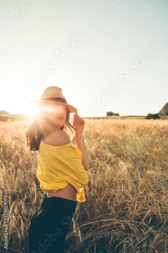 Tela Ragazza con vestito giallo e cappello in un campo di grano sorride felice