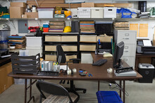 Messy Garage Warehouse Shipping Office With Boxes, Files And Clutter.