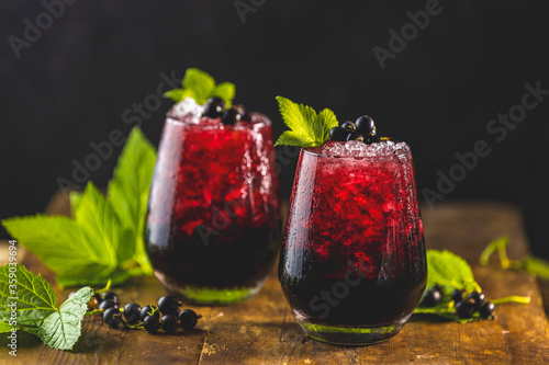 Fototapeta Two glass of cold ice black currant juice or cocktail with ripe berries and green leaves on dark wooden table. Alcohol or non alcohol summer fresh drink obraz
