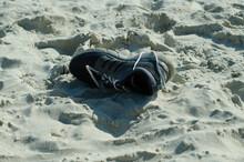 Sneakers. Footwear. The Lost Thing. Garbage On The Beach.