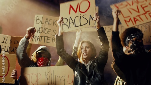 Fotografia Male and female young multiethnic protesters in smoke screaming mottos and slogans with posters for black people dignity at manifestation at night