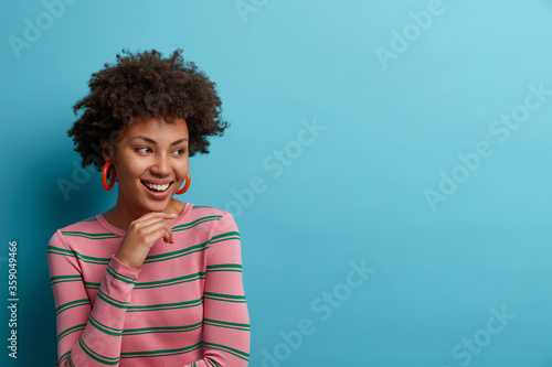 Fototapeta Glad curly young woman keeps hand under chin, smiles carefree, poses with joyful