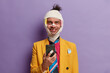 canvas print picture - Addicted drunk man beaten friends, uses mobile phone for online communication, smiles and shows lack of teeth, dressed in formal yellow jacket, wrapped bandage over head, isolated on purple wall