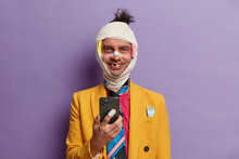 Addicted Drunk Man Beaten Friends, Uses Mobile Phone For Online Communication, Smiles And Shows Lack Of Teeth, Dressed In Formal Yellow Jacket, Wrapped Bandage Over Head, Isolated On Purple Wall