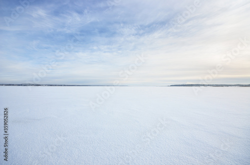 Frozen snow-covered lake under a clear blue sky with cirrus clouds. Fresh snow texture. Arctic, Lapland. Global warming, winter sport and fishing, environmental conservation theme