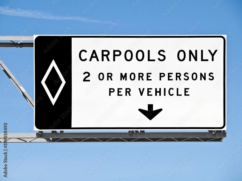 Fototapeta Overhead freeway carpool only sign with blue sky.