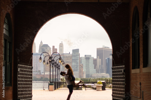 Photo Young boy holding his girlfriend while they are seeing ich other in a big city as anew York