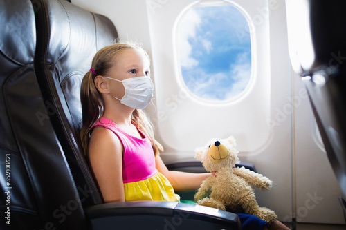 Child in airplane in face mask. Virus outbreak.