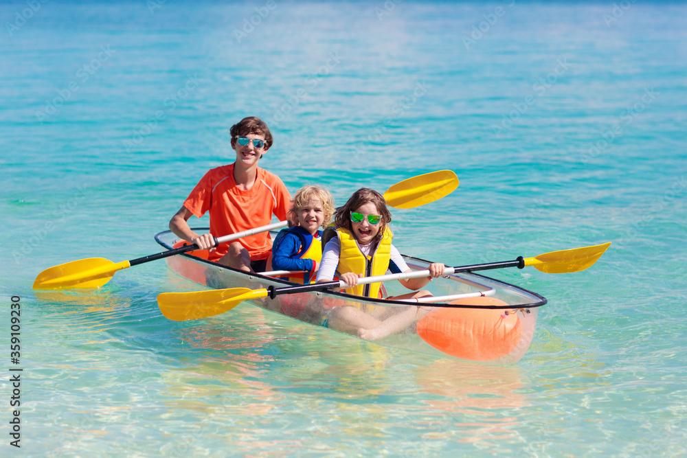 Fototapeta Kids kayaking in ocean. Family in kayak in tropical sea