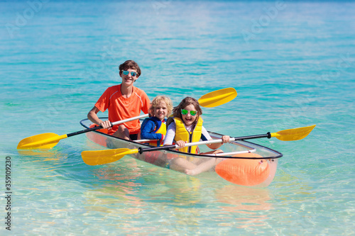 Kids kayaking in ocean. Family in kayak in tropical sea