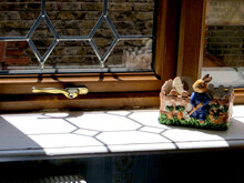 Sunlight Falls On The Window Sill Through A Delicately Glazed Window, A Ceramic Figure Of A Garden-caring Hare Stands On The Windowsill