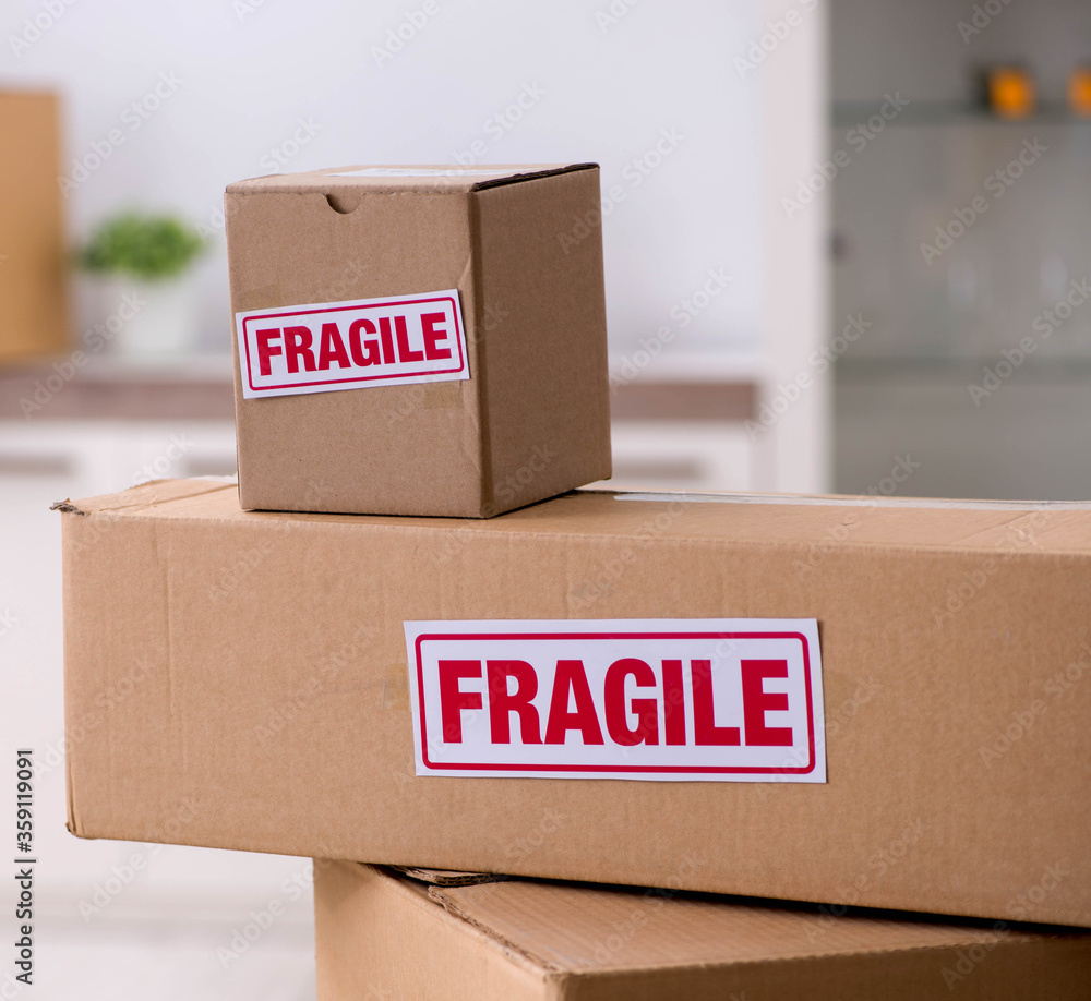 Fototapeta Man moving house and relocating with fragile items