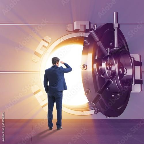 Businessman in front of banking vault door Fototapeta