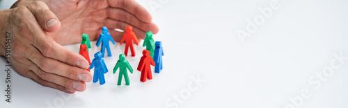 Obraz Business Executive Hand Protecting Employee Figures - fototapety do salonu