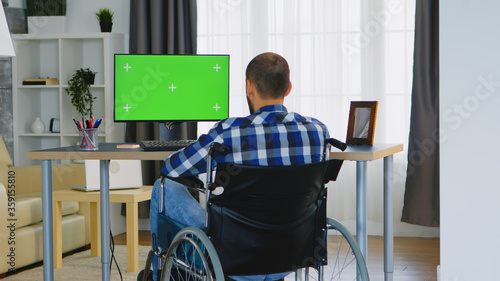 Businessman in wheelchair in front of computer with green screen. Wallpaper Mural