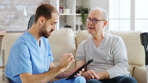 Caucasian male nurse talking with a nursing home patient about his health Slika na platnu