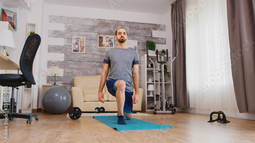 Photo Fit man training his legs doing forward lunges on yoga mat at home