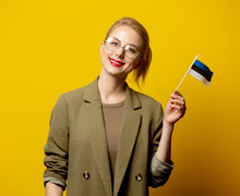 Style Blonde Woman In Jacket With Estonian Flag On Yellow Background