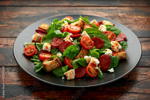 Fotografía Chorizo Tomato salad with spinach, feta cheese and croutons on black plate