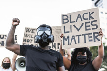 People From Different Culture And Races Protest On For No Racism And Equal Rights - Demonstrators Wearing Face And Gas Masks During Black Lives Matter Fight Campaign - Focus On Black Man With Gas Mask