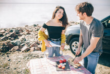 Travel, Tourism - Man And Woman Drink Champagne Near The Water At A Folding Portable Table. Picnic Near The Water. Couple Going On Adventure. Car Travel Concept.