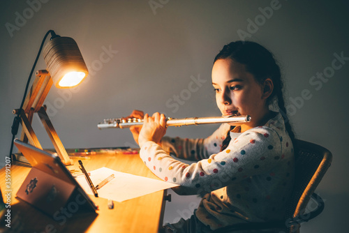 Photo Remote music lesson. Girl playing the flute at home at the night.