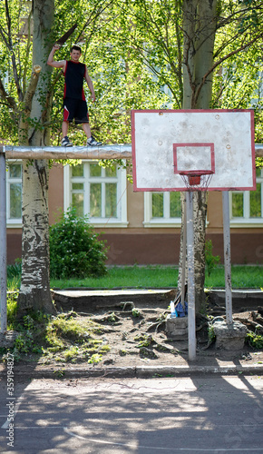 Photo Young man trimming poplar branches over a summer basketball court