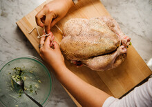 A Woman's Hands Trussing A Chicken Stuffed With Herbs And Vegetables