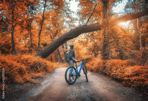 Fotografija Woman riding a bicycle in  forest in autumn at sunset