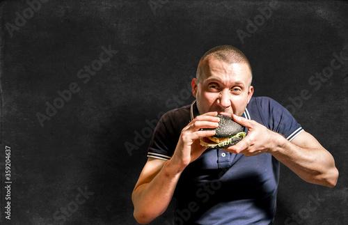 A hungry Man enjoys eating a black Burger #359204637