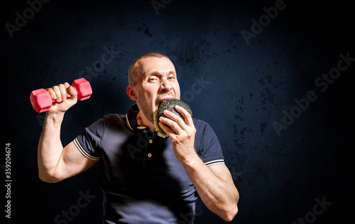 A hungry Man enjoys eating a black Burger and holding a dumbbell . #359204674