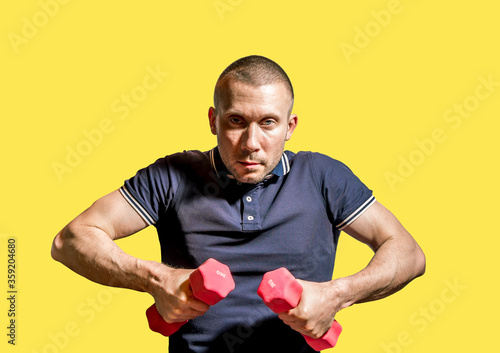 A stern Man holds dumbbells in his hands . #359204680