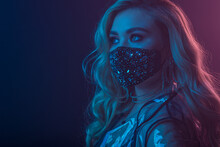 Fashionable Woman Wearing Trendy Luxury Face Safety Black Mask With Rhinestones, Posing In Colorful Bright Neon Uv Blue, Red Lights. Stylish Outfit During Quarantine Of Coronavirus. Copy, Empty Space