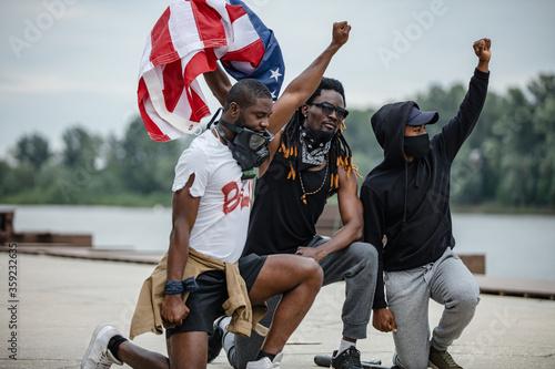 Three protestors kneeling while holding American flag Canvas Print
