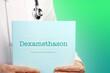 canvas print picture - Dexamethason (COVID-19). Arzt (männlich) mit Stethoskop hält medizinischen Bericht in den Händen. Ausgeschnitten. Hintergrund grün/türkis. Text auf Dokument. Gesundheitswesen/Medizin