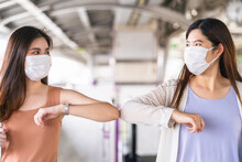 Young Asian Woman Passenger Wearing Surgical Mask And Elbows Bump With Friend Together In Subway Train When Traveling In Big City At Covid19 Outbreak, Infection And Pandemic, New Normal Concept