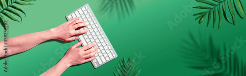 Person using a computer keyboard with tropical leaves and shadow Slika na platnu