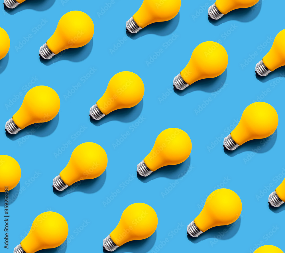 Fototapeta Yellow light bulb pattern with shadow - flat lay