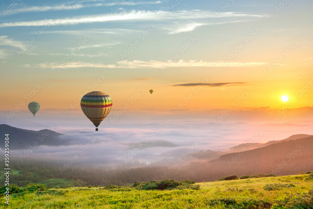 Fototapeta Big hot air baloons over idyllic landscape with green grass covered morning mountains with distant peaks and wide valley full of thick white cloudy fog.
