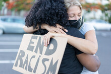 Young African Woman Hugging A Caucasian Northern Woman After A Protest - White Woman With End Racism Bannner In Her Hands - Concept Of Human Rights And Stop Racism