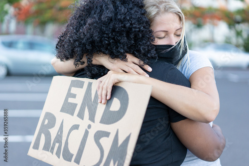 Obraz na plátne Young african woman hugging a caucasian northern woman after a protest - White w
