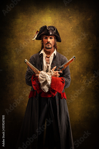 Fotografie, Obraz Portrait of a pirate, holding two musket pistol in his hands
