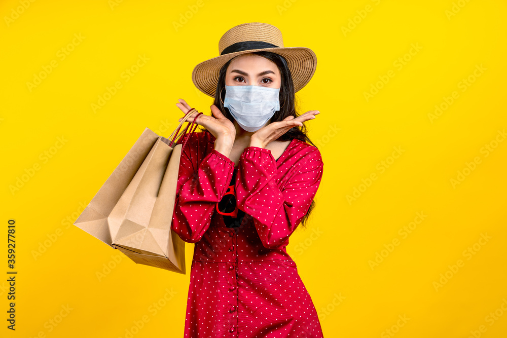 Fototapeta Portrait of young happy carefree asian woman wear hat and facemask carrying shop bag smile on isolated color background in concept back to shopping, new normal summer fashion lifestyle after covid19.