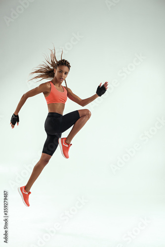 Fototapeta Do it! Full length of young african woman with perfect body in sports clothing j