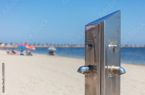 Fotografia, Obraz At the Mar Menor in Spain there is a silver water dispenser for cleaning on the beach