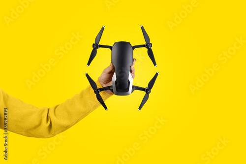 Fotografía drone in hand over yellow background, shooting device concept