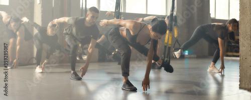 Fototapeta Knockout Fitness. Full-length shot of men and women doing fitness training exercises at industrial gym. Straps, group workout concept obraz